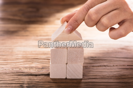 hand holding a roof of wooden