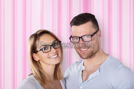 happy young couple wearing eye glasses