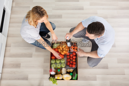 couple with groceries in the cardboard