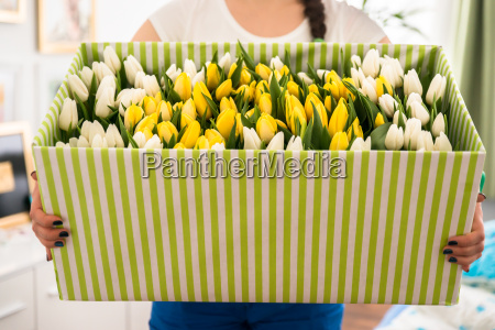 woman holding tulips in the box
