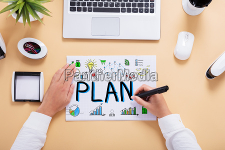 businessperson drawing plan chart on office