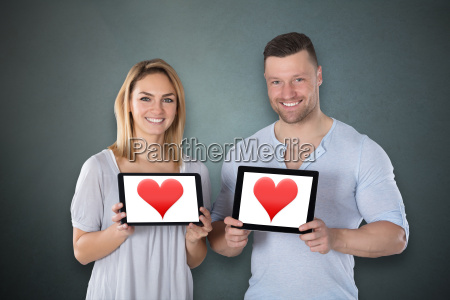 couple showing heart on digital tablet