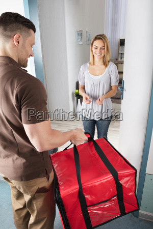 delivery man giving bag to woman