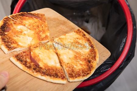 person wirft pepperoni pizza in dustbin