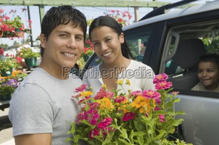 couple loading plants into minivan at