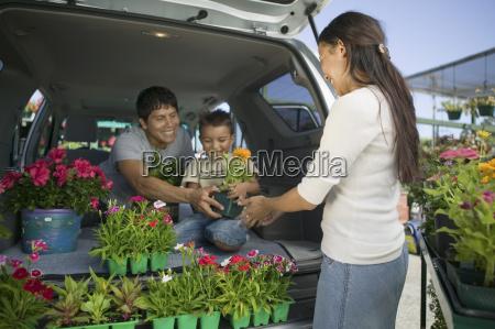 family loading flowers into minivan