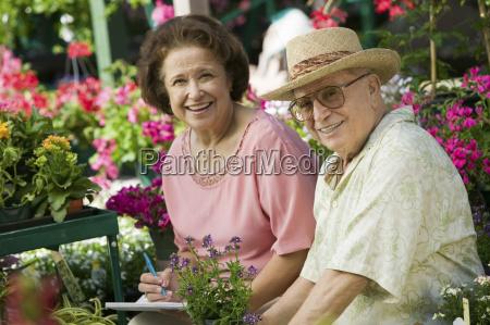 couple buying plants in nursery