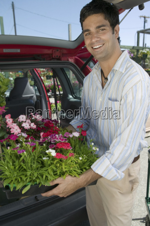 man loading flowers into back of
