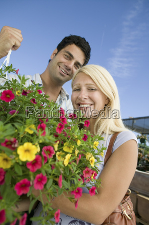 couple standing in plant nursery holding