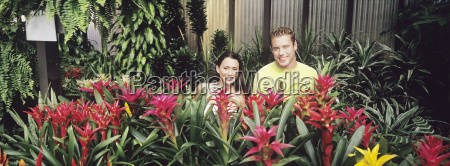 couple standing among plants in plant