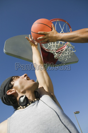 man playing basketball with friend against