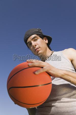 young man holding basketball low angle