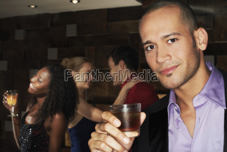 man holding drink with people dancing