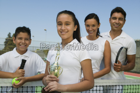 tennis family on court by net