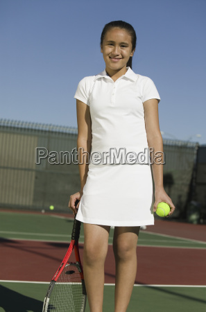 young female tennis player standing on