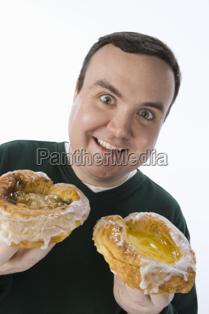 obese man holding two donuts