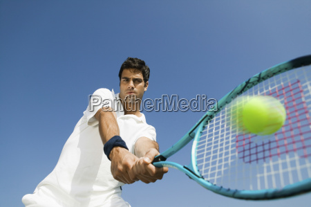 determined man playing tennis against sky