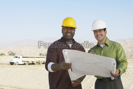 engineers with blueprint at construction site