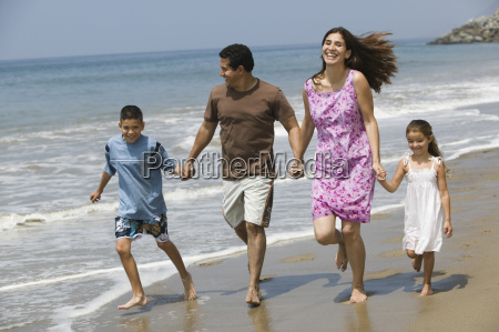family holding hands while running on