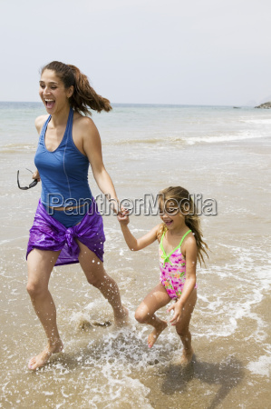 mother and daughter running through water