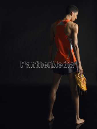 full length of male athlete holding