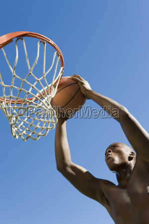 man dunking basketball into hoop against