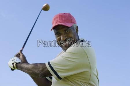 senior man swinging a golf club