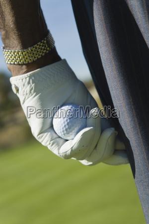 mans hand holding golf ball