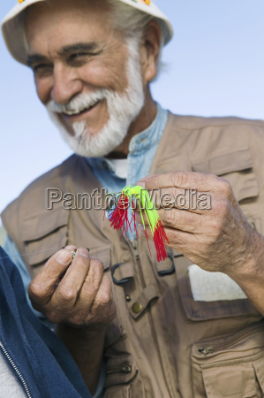man tying a fly fishing lure
