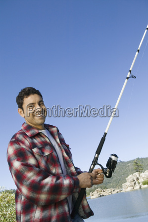 man fishing nearby a lake