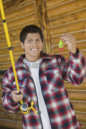 man holds a fishing rod and