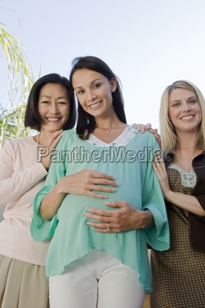 pregnant woman and friends smiling