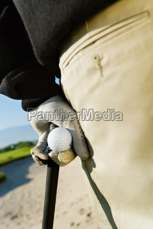 male golfer holding golf club and
