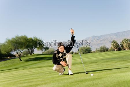männlicher, golfspieler, der, putt, ausrichtet - 21390977
