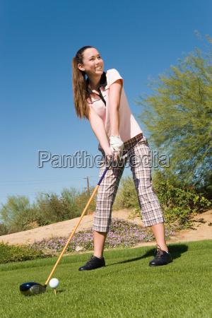 weiblicher golfer teeing off