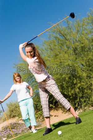 glueckliche junge frau die golf spielen