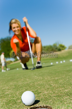 female golfer looking at ball rolling