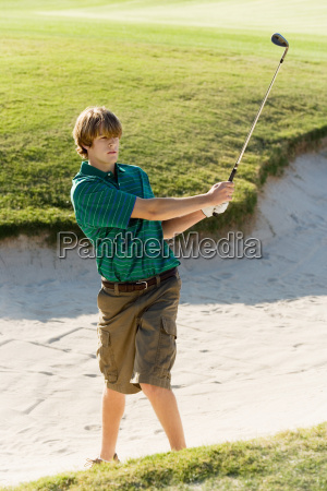 golfer hitting golf ball out of