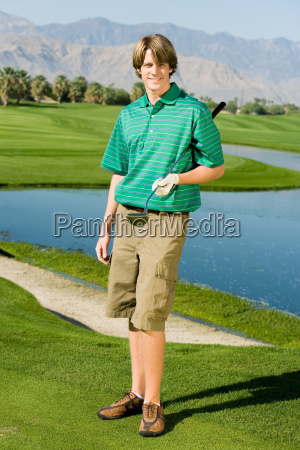 happy young man with golf club