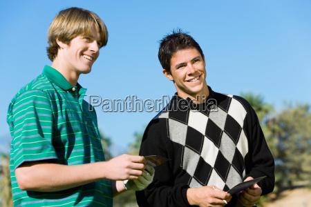 zwei maennliche golfspieler die nebeneinander stehen