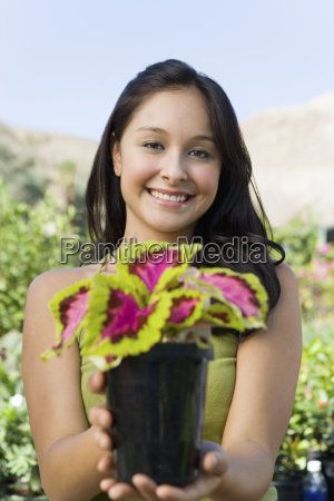 happy young woman holding potted plant