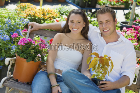 couple with flower plants sitting on