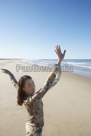 cheerful teenage girl running across beach