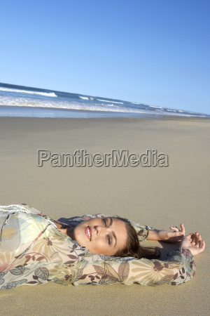 beautiful teenage girl lying on sandy