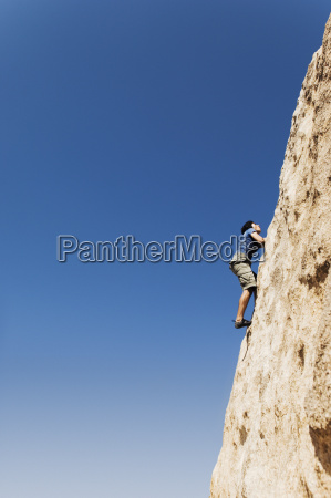 woman free climbing on cliff