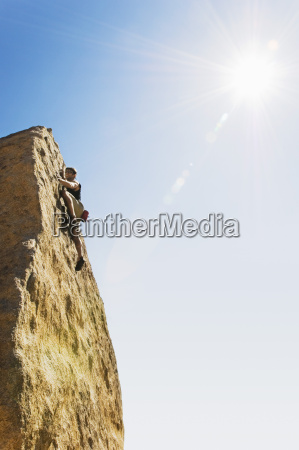 man free climbing on cliff