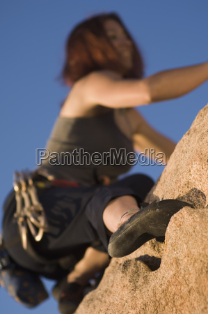 female hiker climbing on a cliff