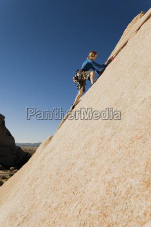woman climbing rock against clear blue