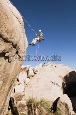 man rappelling from cliff