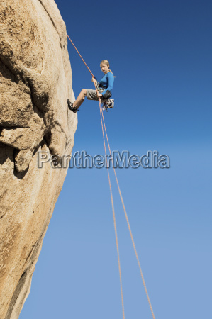woman rappelling from cliff